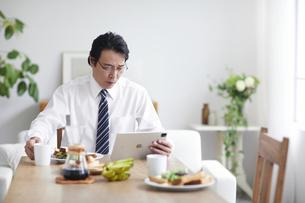 タブレット端末を見ながら朝食をとる男性の写真素材 [FYI04881355]
