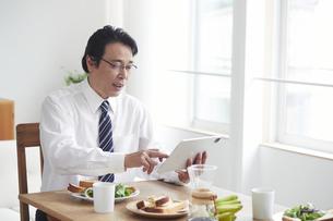 タブレット端末を見ながら朝食をとる男性の写真素材 [FYI04881356]
