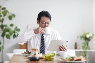 タブレット端末を見ながら朝食をとる男性の写真素材 [FYI04881357]