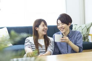 リビングでくつろぐ仲の良い日本人の男女の写真素材 [FYI04881419]