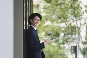 スマートフォンを見る若い男性・ビジネスマンが出社してIoTをするイメージの写真素材 [FYI04882225]