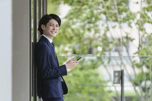 スマートフォンを見る若い男性・ビジネスマンが出社してIoTをするイメージの写真素材 [FYI04882226]