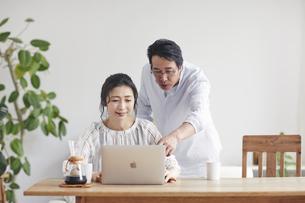 リビングでパソコンを見る夫婦の写真素材 [FYI04882616]