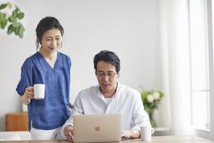 リビングでパソコンを見る夫婦の写真素材 [FYI04882619]