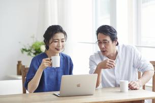 リビングでパソコンを見る夫婦の写真素材 [FYI04882628]