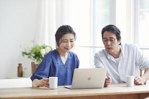 リビングでパソコンを見る夫婦の写真素材 [FYI04882635]