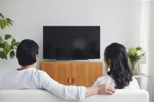 リビングでテレビを見ながらくつろぐ夫婦の後ろ姿の写真素材 [FYI04882656]