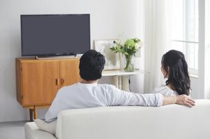 リビングでテレビを見ながらくつろぐ夫婦の後ろ姿の写真素材 [FYI04882660]