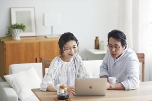 リビングでパソコンを見る夫婦の写真素材 [FYI04882665]