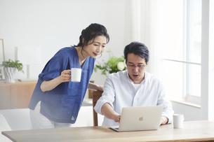 リビングでパソコンを見る夫婦の写真素材 [FYI04882673]