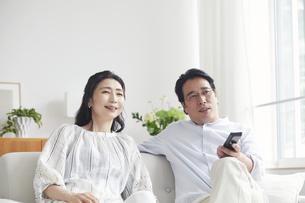 リビングでテレビを見ながらくつろぐ夫婦の写真素材 [FYI04882675]