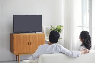 リビングでテレビを見ながらくつろぐ夫婦の写真素材 [FYI04882676]