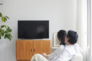 リビングでテレビを見ながらくつろぐ夫婦の写真素材 [FYI04882678]