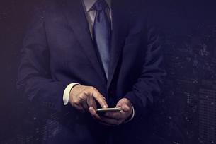 スマートフォンを操作するビジネスマンの写真素材 [FYI04883065]