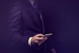 スマートフォンを操作するビジネスマンの写真素材 [FYI04883075]