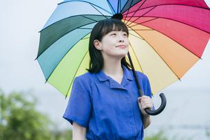 雨の中、カラフルな傘を指す女性の写真素材 [FYI04883329]