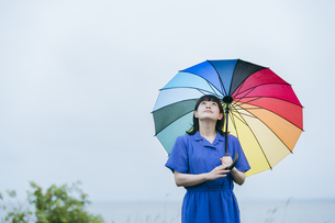 雨の中、カラフルな傘を指す女性の写真素材 [FYI04883331]