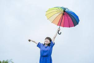 雨の中、カラフルな傘を指す女性の写真素材 [FYI04883336]