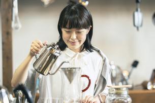 落ち着いた空間で、コーヒーを淹れる若い女性の写真素材 [FYI04883337]