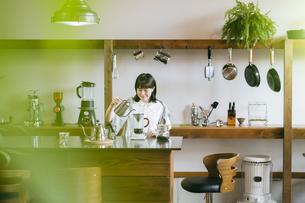 落ち着いた空間で、コーヒーを淹れる若い女性の写真素材 [FYI04883339]