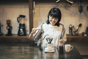 落ち着いた空間で、コーヒーを淹れる若い女性の写真素材 [FYI04883340]