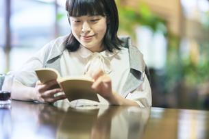 暖かい雰囲気の空間で、本を読む若い女性 の写真素材 [FYI04883344]