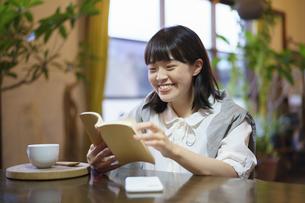 暖かい雰囲気の空間で、本を読む若い女性 の写真素材 [FYI04883352]