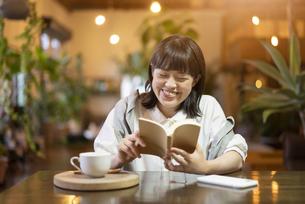 暖かい雰囲気の空間で、本を読む若い女性 の写真素材 [FYI04883355]