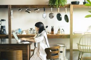 暖かい雰囲気の空間で、ノートパソコンの画面を見る女性の写真素材 [FYI04883358]