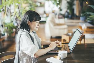暖かい雰囲気の空間で、ノートパソコンの画面を見る女性の写真素材 [FYI04883364]