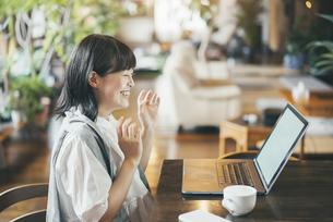 暖かい雰囲気の空間で、ノートパソコンの画面を見る女性の写真素材 [FYI04883366]