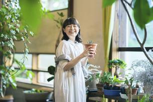 笑顔で観葉植物の様子を見る若い女性の写真素材 [FYI04883378]