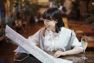 おしゃれな空間で、地図を見る若い女性の写真素材 [FYI04883427]