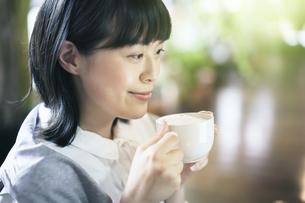 暖かい雰囲気の空間で、コーヒーを飲む若い女性の写真素材 [FYI04883435]