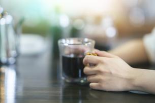 暖かい雰囲気の空間で、コーヒーを飲む若い女性の写真素材 [FYI04883436]
