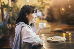暖かい雰囲気の空間で、コーヒーを飲む若い女性の写真素材 [FYI04883439]
