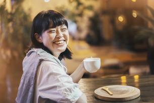 暖かい雰囲気の空間で、コーヒーを飲む若い女性の写真素材 [FYI04883443]
