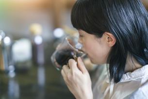 暖かい雰囲気の空間で、コーヒーを飲む若い女性の写真素材 [FYI04883446]