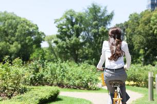自転車に乗るビジネスウーマンの後姿の写真素材 [FYI04883974]