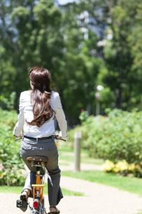 自転車に乗るビジネスウーマンの後姿の写真素材 [FYI04883975]