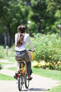 自転車に乗るビジネスウーマンの後姿の写真素材 [FYI04883977]