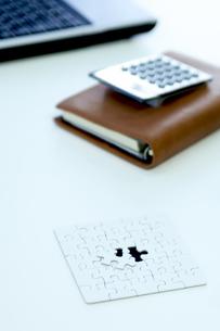机の上のパズルと手帳と電卓の写真素材 [FYI04884072]