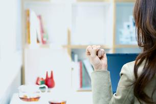 デスクでガッツポーズをするビジネスウーマンの写真素材 [FYI04884164]
