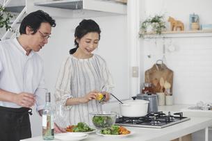 キッチンで料理を作る夫婦の写真素材 [FYI04884484]