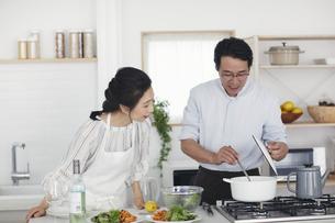 キッチンで料理を作る夫婦の写真素材 [FYI04884487]
