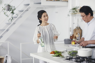 キッチンで料理を作る夫婦の写真素材 [FYI04884491]