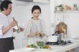 キッチンで料理を作る夫婦の写真素材 [FYI04884493]