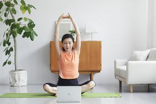ノートパソコンを見ながらリビングで運動をする女性の写真素材 [FYI04884495]