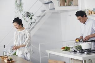 キッチンで料理を作る夫婦の写真素材 [FYI04884496]