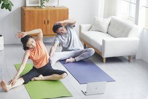 ノートパソコンを見ながらリビングで運動をする夫婦の写真素材 [FYI04884497]
